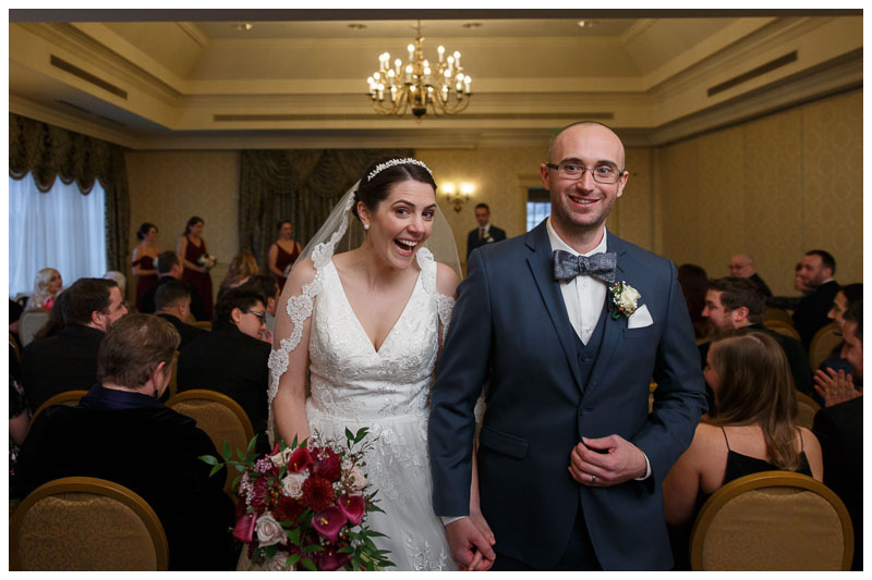 Bride and Groom walkin down the aisle in the ballroom at the inn on Boltwood