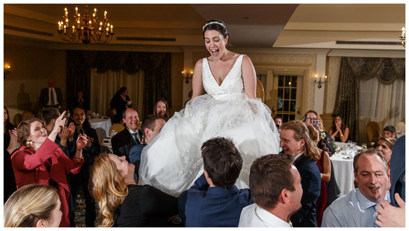 Bride raised up in the air on a chair during huppa dance