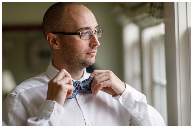 Groom getting ready fixing bow tie in front of window.